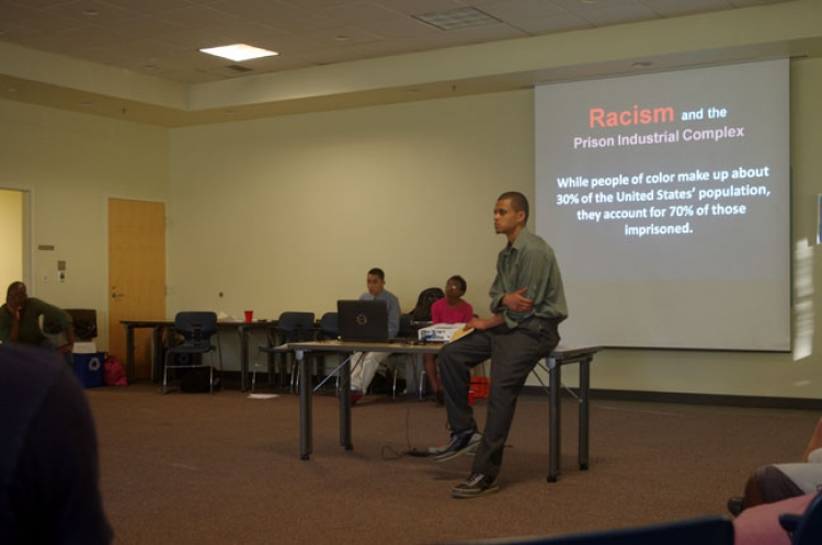 Person from Youth Undoing Institutional Racism presents at the front of a class
