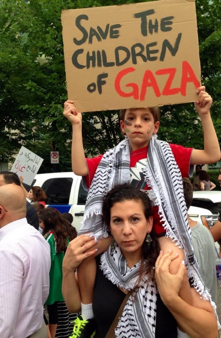 "Zeina with her son Mejd who is holding a sign that says ""Save the children of Gaza"""