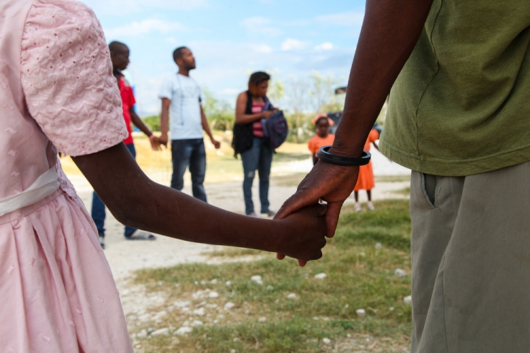 People holding hands in a circle in Haiti