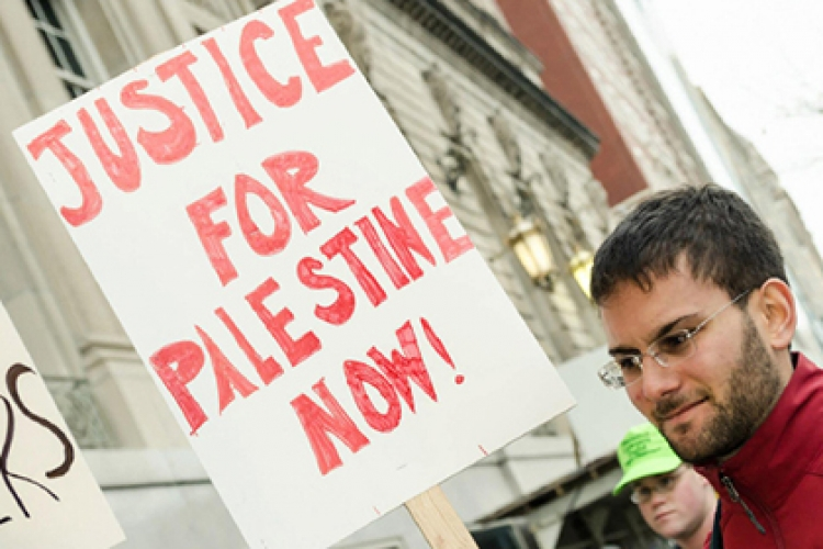 """Protester holding a """"Justice for Palestine"""" sign"""