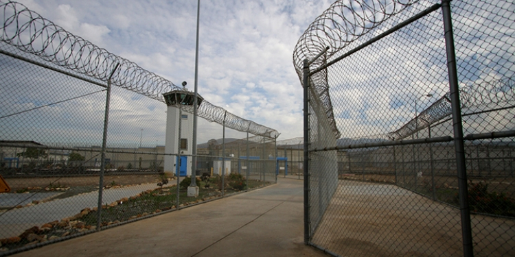 Prison fence lined with barbed wire and a watch tower