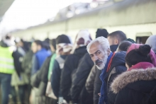 Syrian refugees waiting in line for a train