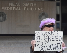 "Woman with sign reading, ""Corporate Greed hurts democracy"""