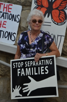 """Woman with sign reading, """"Stop separating families"""""""