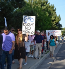 """line of protestors, one holding a sign that reads, """"God knows no borders"""""""