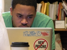 Man looks at laptop screen with a no new prisons sticker