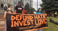 People with Defund Hate Invest Love banner