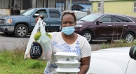 A community member receives a donation of food at a neighborhood event.