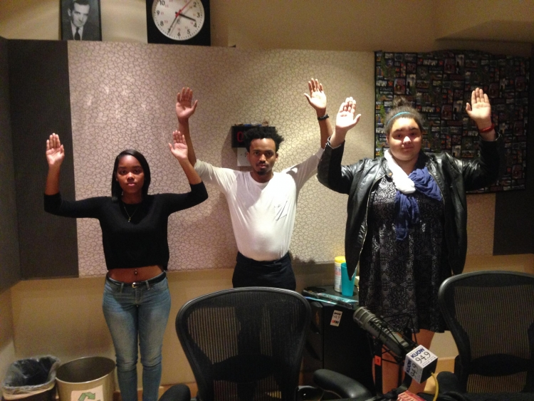 three young people with hands up