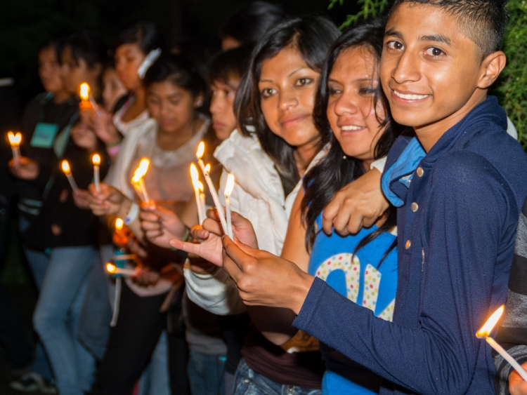 Young people holding candles at vigil