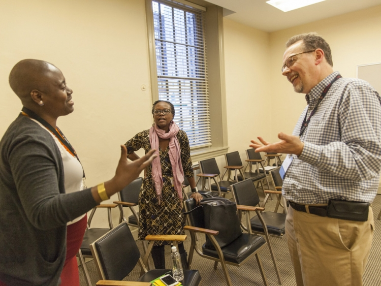 Alissa Wilson, Rachel Madenyika, and Andrew Tomlinson chat after their Shared Security workshop