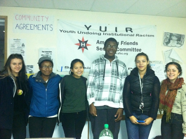 group stands in front of YUIR sign (youth undoing institutional racism)