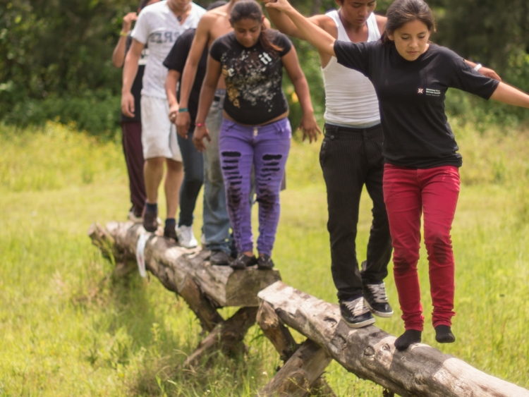 Young people walking along a log