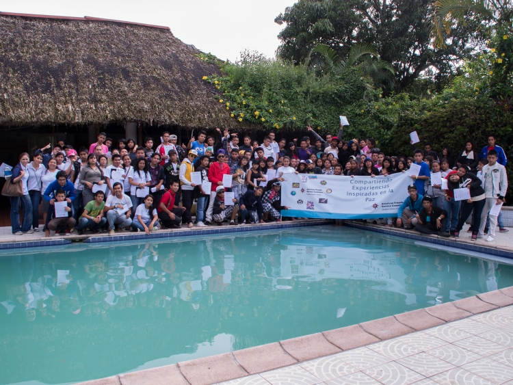 Group photo of camp participants standing behind a pool
