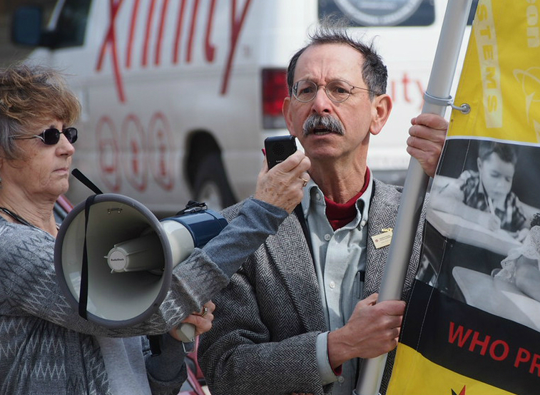 Arnie Alpert demonstrates against corporate influence on public policy in the lead-up to the 2016 presidential primary races. Photo: AFSC