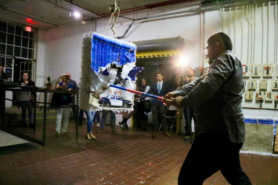 At a State of the Union watch event in San Diego, AFSC staffer Benjamin Prado takes a swing at a pinata of the border wall. Photo: Pedro Rios/AFSC
