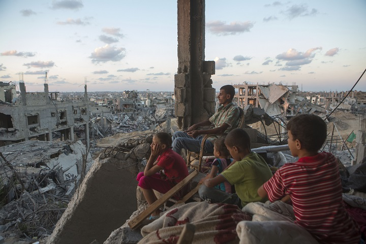 Family in a destroyed house in the At-Tuffah district in Gaza after the 2014 bombardment of Gaza, photo by Anne Paq of ActiveStills