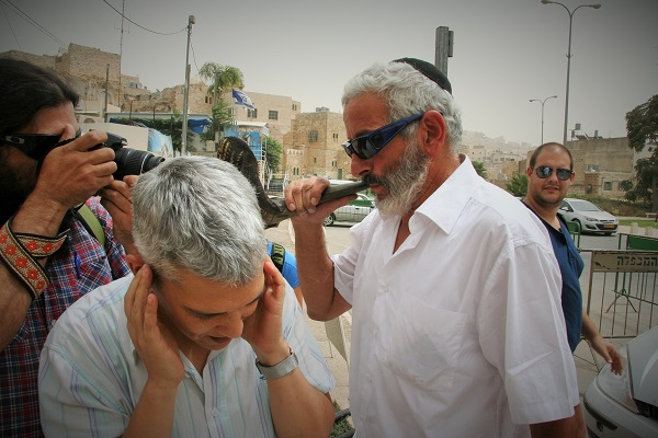 An Israeli settler blows his shofar after aggressively shoving my colleague Dalit.  According to Palestinian shopkeepers, he had been there all day disrupting the calls to prayer.